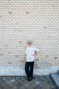 Woman standing by brick wall
